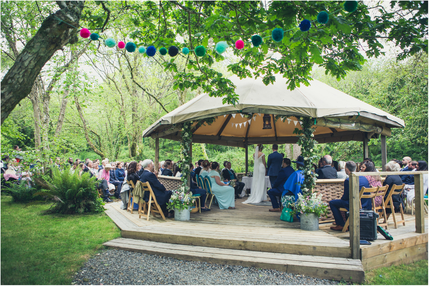2 Guests seated outside for woodland wedding ceremony