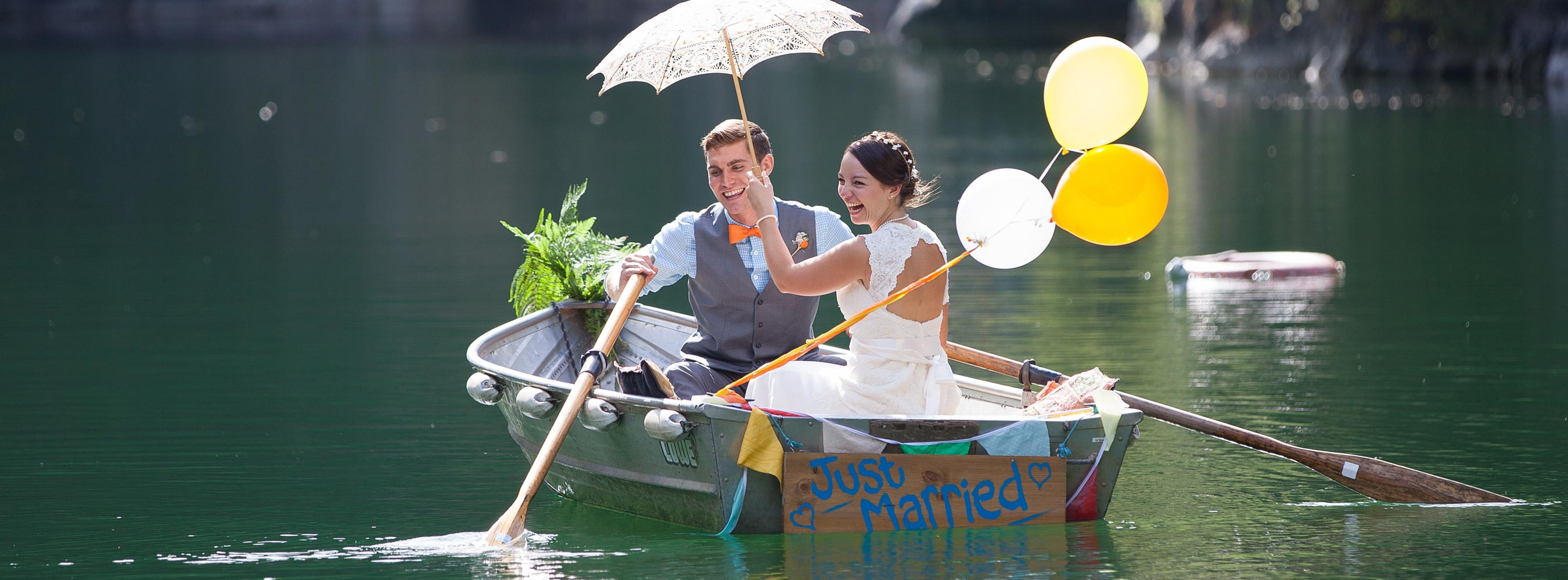 Bride and Groom in a boat at Lake with balloons